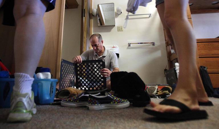 In this Aug. 16, 2010, file photo, Paul Kramer, of Chicago, puts together a shoe organizer as he helps his daughter Ariana move into her dorm room at the University of Iowa in Iowa City. (AP File)