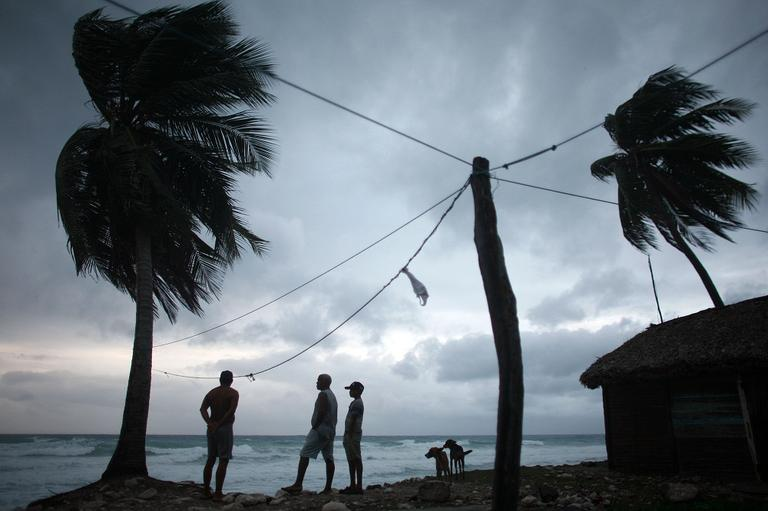 People look out at the beach as Tropical Storm Isaac approaches in Barahona, Dominican Republic, Friday. (AP)