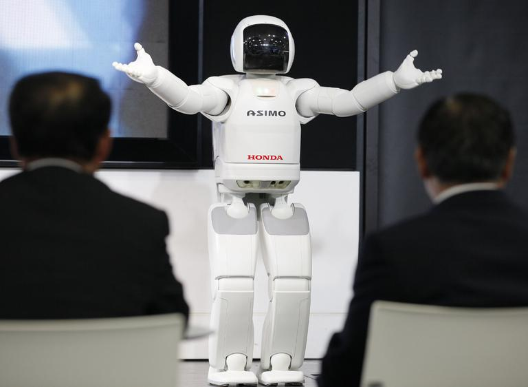 Visitors watch a Honda Asimo robot performing at the headquarters of Honda Motor Co. in Tokyo. Canon Inc. is moving toward fully automating digital camera production in an effort to cut costs. (AP)