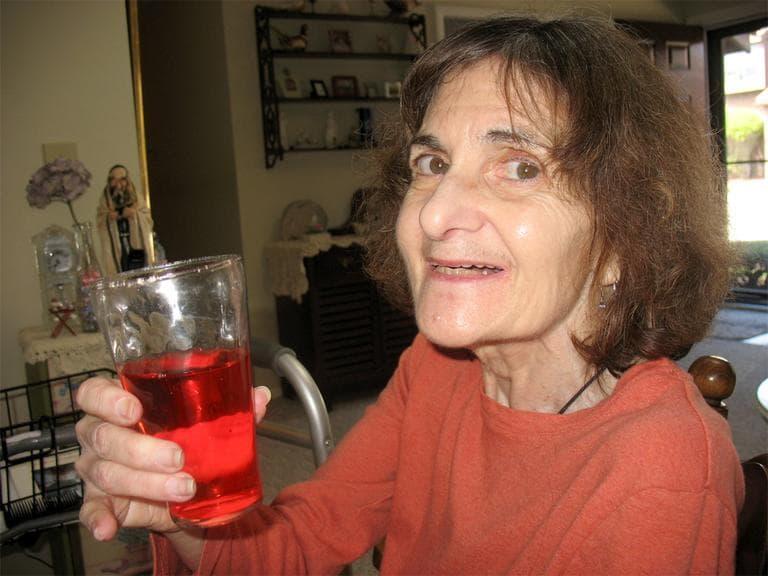 Sue Beder, with diet cranberry juice, in her Stoughton living room (Martha Bebinger/WBUR)