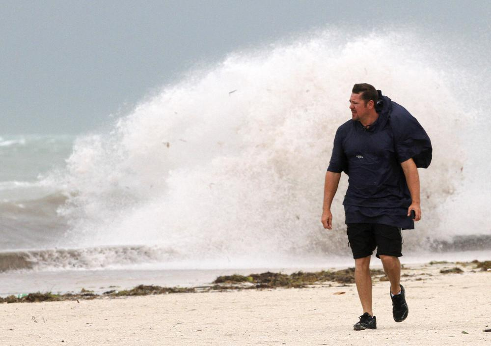A man walks on the beach in Key West, Fla. as heavy winds hit the northern coast from Tropical Storm Isaac. (AP)