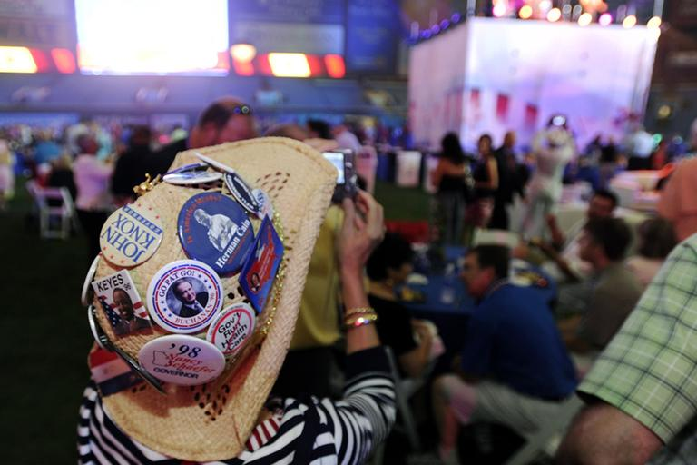Judy Griffin, of Georgia, takes photos while wearing a hat with Republican Party buttons during the 2012 Tampa Bay Host Committee's welcoming event for the delegates of the Republican National Convention on Sunday, Aug. 26, 2012 at Tropicana Field in St. Petersburg, Fla. (AP)