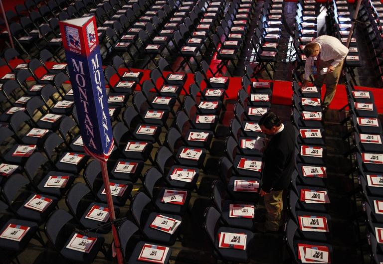 A volunteer places pamphlets on chairs in Montana's delegation seating area before the start of the Republican National Convention in Tampa, Fla., on Tuesday. (AP/Lynne Sladky)