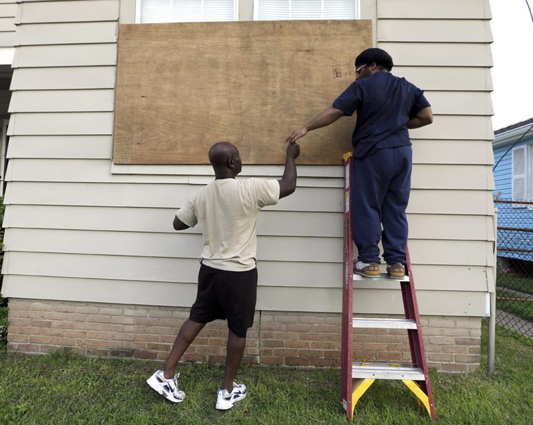 Stacey Davis, left, hands a screw to his son as they board up windows on their home before Tropical Storm Isaac hits in New Orleans. (AP)