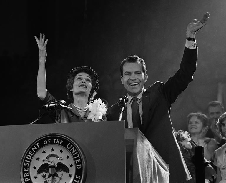 Mrs. Nixon glances up and Vice President Nixon waves to Republican convention from rostrum in Chicago on July 29, 1960. He came before convention to accept presidential nomination. (AP)