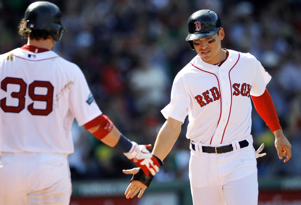 Jacoby Ellsbury, right, celebrates with Jarrod Saltalamacchia as he scores on a double hit by Cody Ross in the sixth inning Monday in Boston. The Red Sox won 5-1. (AP)