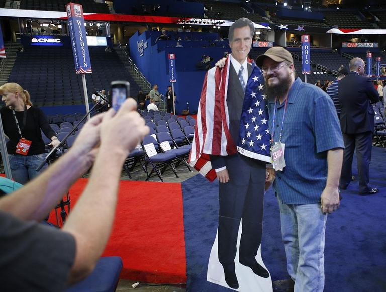 Travis Chapin from St. Petersburg, Fla., poses for a picture with a life-size picture figure of Mitt Romney on the floor at the Republican National Convention in Tampa, Fla., on Wednesday. (AP/Jae C. Hong)