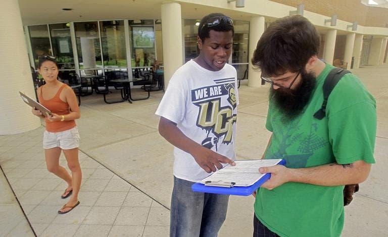 Jordan Allen, center, helps student Casey Eirhstaedt, right, register to vote at the University of Central Florida in Orlando, Fla. (AP/John Raoux)