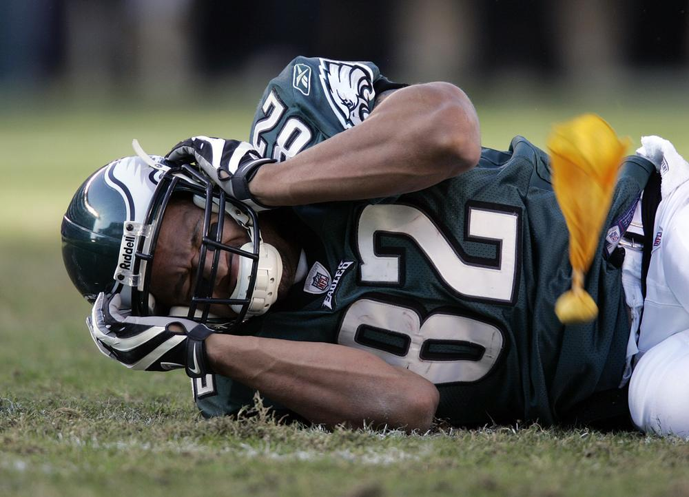 As the 2012 NFL season gets underway, commentator Bill Littlefield explores the consequences of our national obsession. In this Oct. 26, 2008 photo Philadelphia Eagles tight end L.J. Smith holds his head after a hard hit that resulted in a concussion. (AP File Photo)