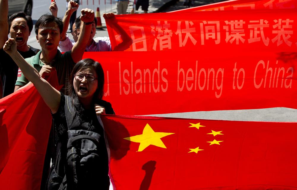"Anti-Japan protesters shout slogans while marching outside Japanese Embassy with Chinese national flags and banners in Beijing, China, Sunday, Aug. 19, 2012. One of the banners reads ""Diaoyu Islands belong to China since 1372! "" A group of Japanese activists swam ashore and raised flags early Sunday on one of a group of islands at the center of an escalating territorial dispute with China. (AP)"