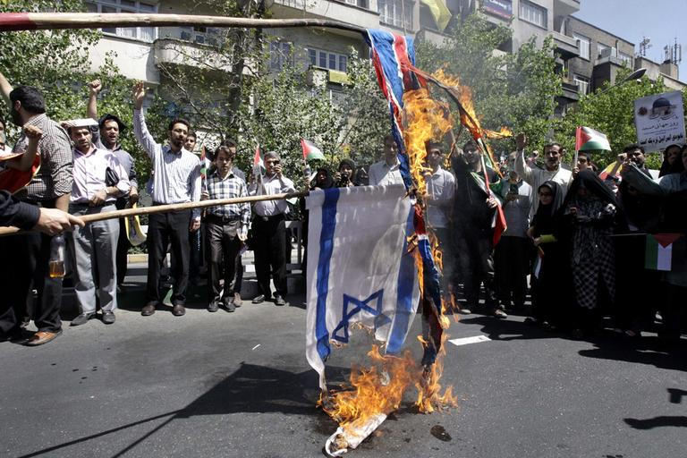 Iranian demonstrators burn an Israeli and British flag during a an annual pro-Palestinian rally marking Quds (Jerusalem) Day, on the last Friday of the holy month of Ramadan, at the Enqelab-e-Eslami (Islamic Revolution) St. in Tehran, Iran, Friday, Aug. 17, 2012. (AP)