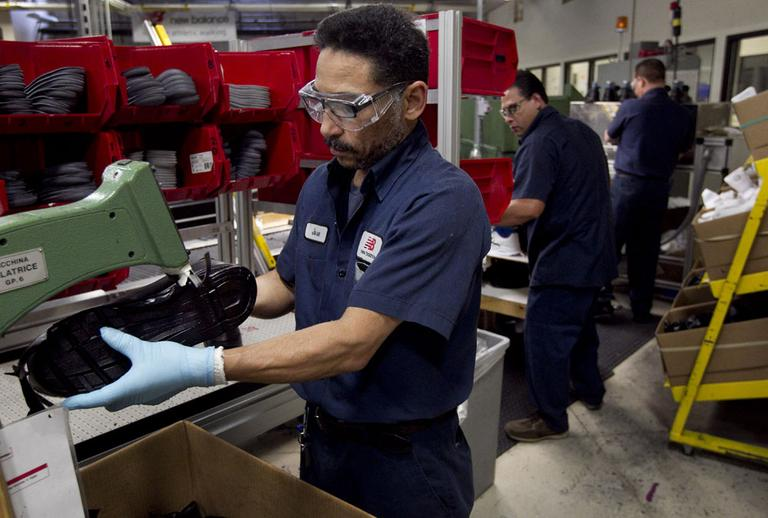 Worker Jose David, of Revere, Mass., left, trims the sole of a shoe during the assembly process at the New Balance Athletic Shoe, Inc. factory in Boston, Tuesday, May 1, 2012. (AP)