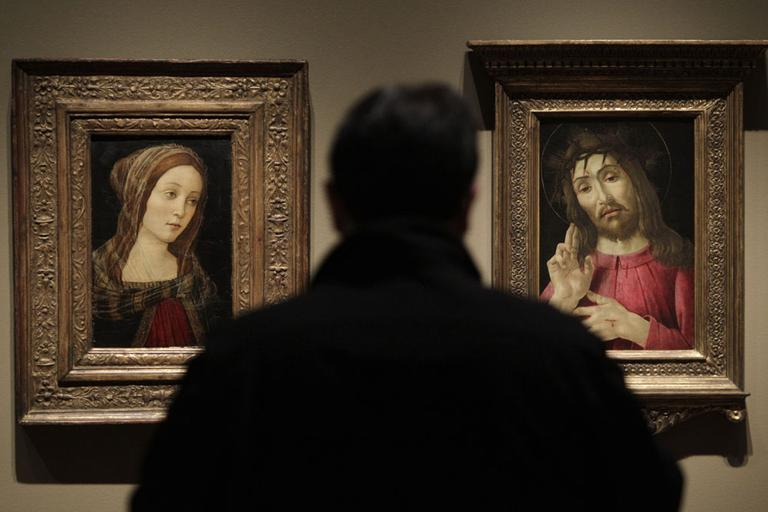 "In an exhibition on forgeries at the Detroit Institute of Arts, a painting titled ""A Female Saint"", left, that once was attributed to Italian artist Sandro Botticelli is exhibited alongside ""The Resurrected Christ,"" right, a Botticelli painting from around 1480. (AP)"