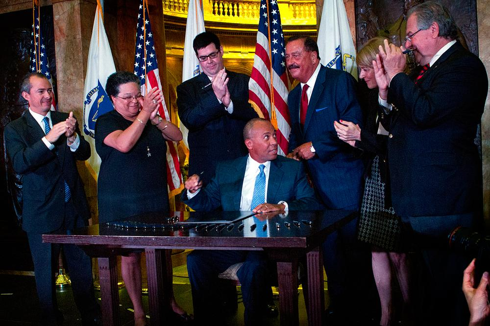 Gov. Patrick signing the health care cost bill earlier today. (Jesse Costa/WBUR)