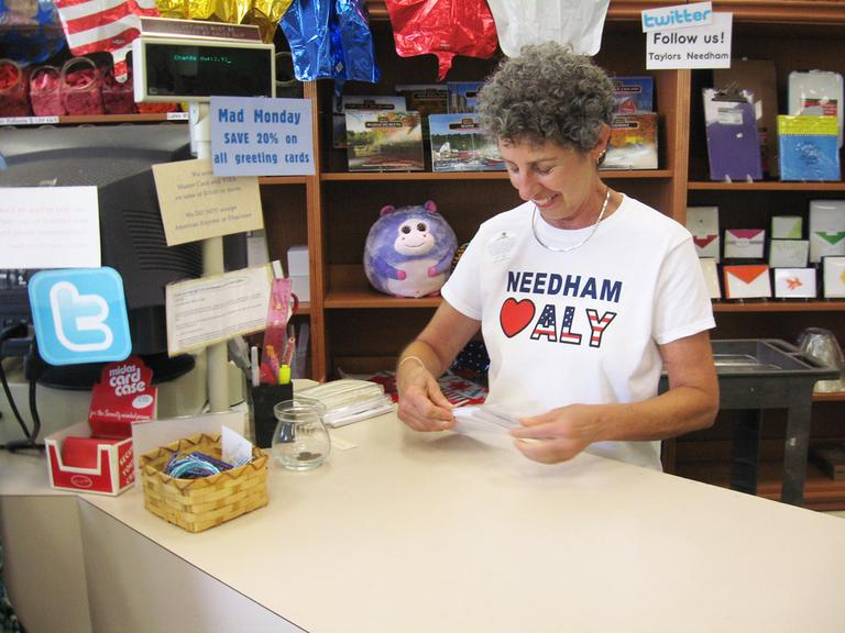 Toby Sandler, an employee at Taylor's Stationery, wearing one of the store's t-shirts supporting Aly Raisman (Lynn Jolicoeur for WBUR)