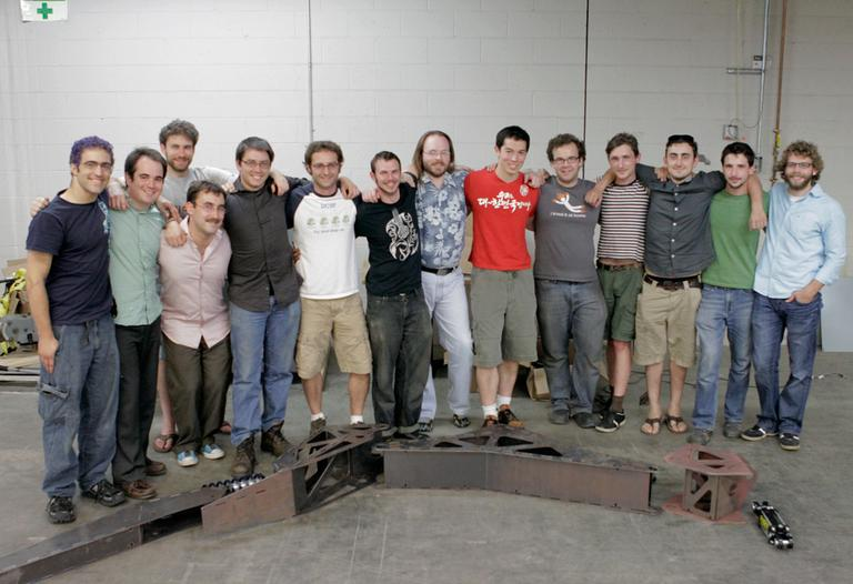 The Project Hexapod class, consisting of 3 instructors, 1 TA, and 15 students standing by a scale model of Stompy's leg (Nate Goldman/WBUR)