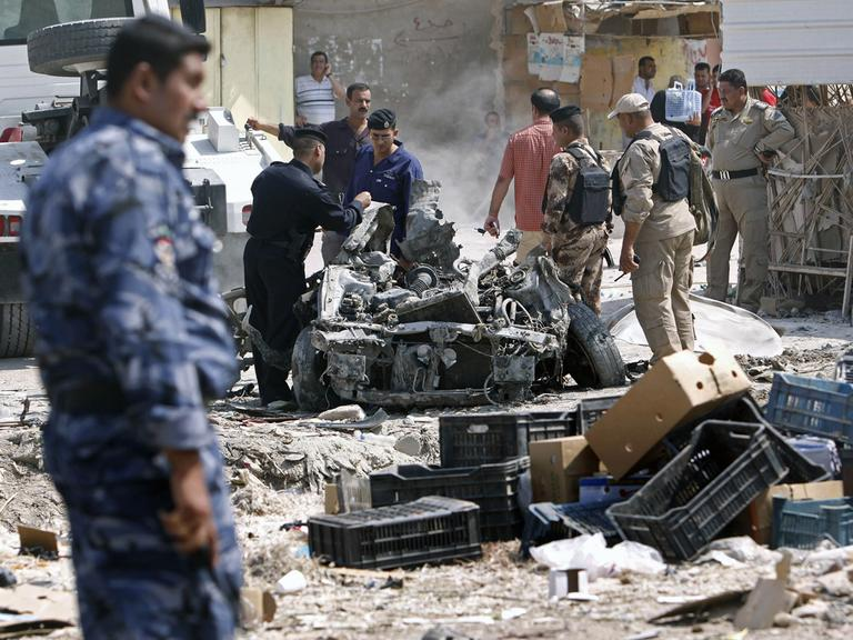 Security forces inspect the scene of a car bomb attack in Basra, 340 miles southeast of Baghdad, Iraq, Sunday, Sept. 9, 2012. (AP)