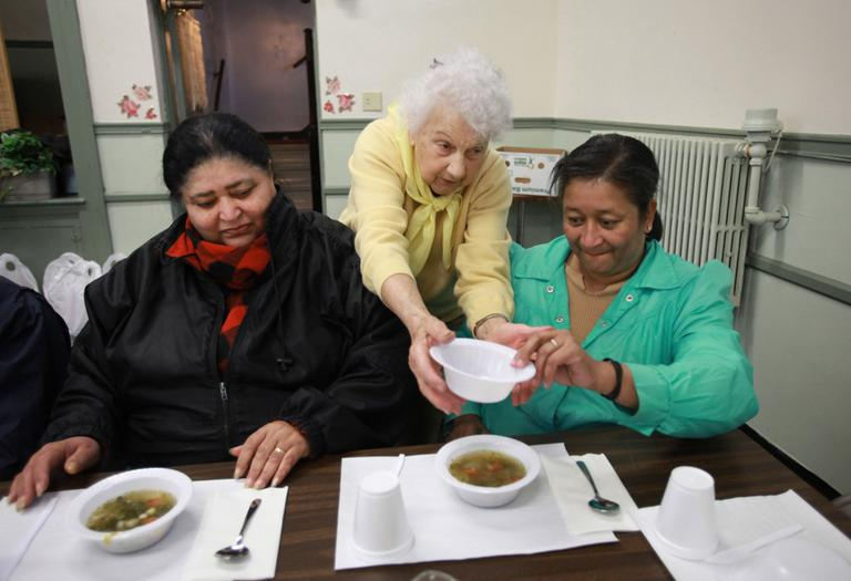 Theresa Martin, a volunteer at the Woodlawn Baptist Church food pantry, delivers soup to Rose Batista, left, and her niece Laura Batista during a service at the food pantry called Bread and Broth for Lent, in Pawtucket in 2009. (AP)