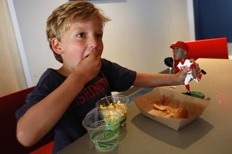 """Bryce Blaylock, 5, of Bristow, Va., eating popcorn inside the """"peanut-free"""" suite section of Nationals Park in Washington. Both Blaylock and his younger brother have peanut allergies that keep them from coming to most games. (AP)"""