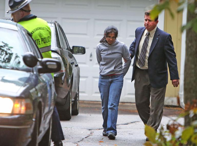 Annie Dookhan, center, is escorted to a cruiser outside her home in Franklin, Mass., on Friday. (AP)