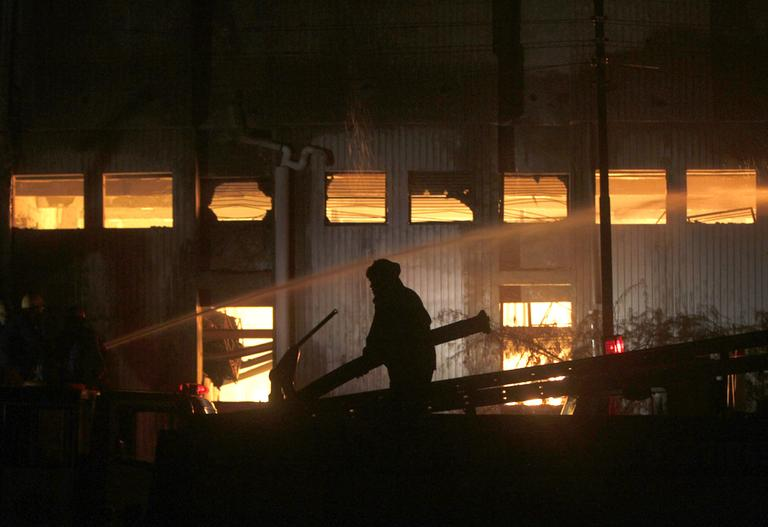A fireman tries to extinguish a fire which broke out in a factory on Tuesday, Sept. 11, 2012 in Karachi, Pakistan. Factory fires in two of Pakistan's major cities killed 39 people and injured dozens more. (AP)