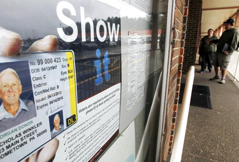 In this file photo people pass the signs telling of the requirement for voters to show an acceptable photo ID to vote as they head into the the Penndot Drivers License Center in Butler, Pa. (AP)