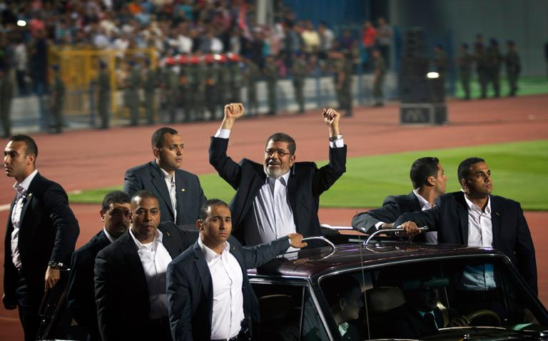 Egyptian President Mohammed Morsi waves to the crowd gathered in a Cairo stadium upon his arrival for a speech on the 6th of October national holiday marking the 1973 war with Israel. (Khalil Hamra/AP)