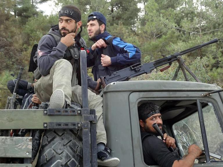 Free Syrian Army fighters sit on top of a military truck that was captured from the Syrian Army in the village off Khirbet al-Jouz, in the northern province of Idlib, Syria. (AP/Edlib News Network)