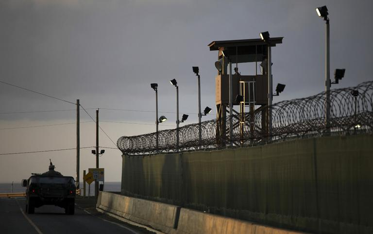 A U.S. trooper stands in the turret of a vehicle with a machine gun, left, as a guard looks out from a tower, in this 2010 photo of Guantanamo Bay U.S. Naval Base in Cuba. (AP/Brennan Linsley)