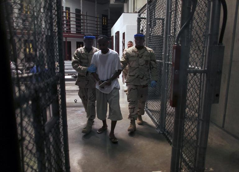 """A Guantanamo detainee carries a workbook as he is escorted by guards after the detainee attended a class in """"Life Skills"""" at Guantanamo Bay detention facility in March 2010. (AP/Brennan Linsley)"""