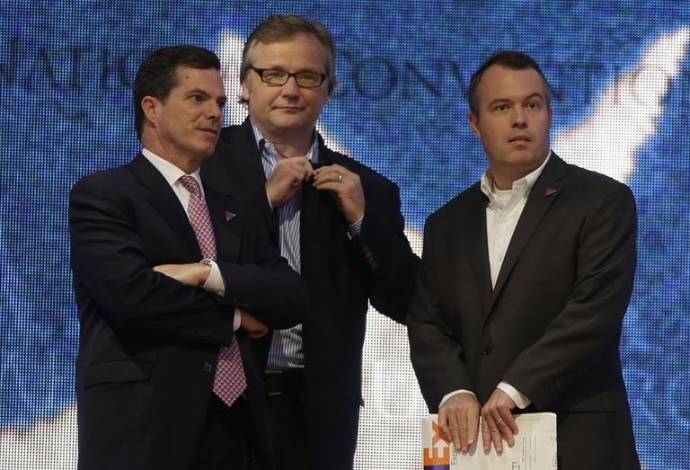 Advisers Peter Flaherty, left, Eric Fehrnstrom center, and campaign manager Matt Rhoades stand on stage as Republican presidential candidate Mitt Romney checks the podium at the Republican National Convention in Tampa, Fla., in August 2012. (AP/Charles Dharapak)