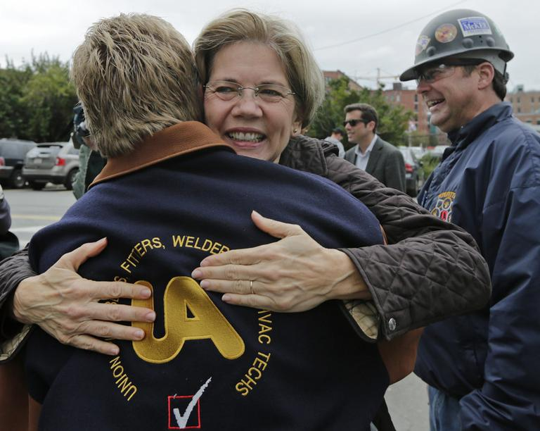 Elizabeth Warren embraces Tom McGrath, of Pipefitters Local 537, while campaigning in Boston on Tuesday. (Charles Krupa/AP)