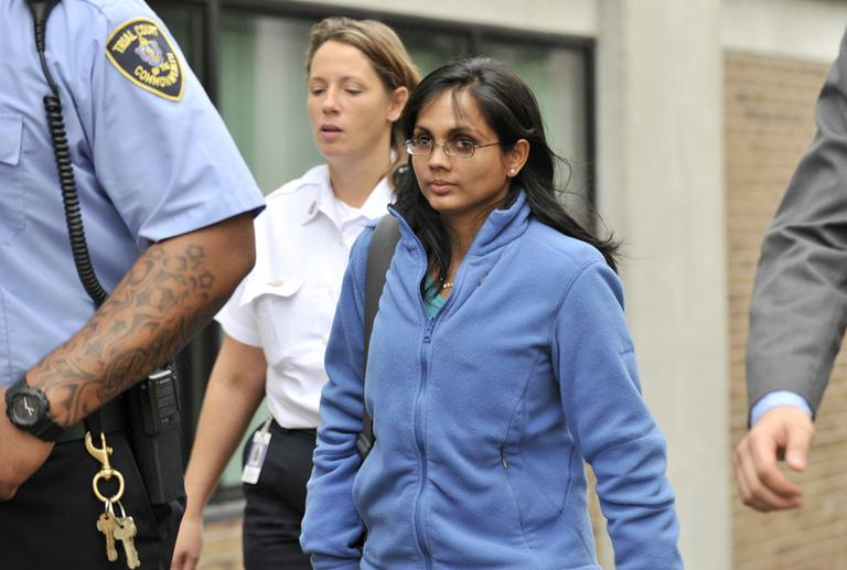 Annie Dookhan, center, leaves a Boston courthouse escorted by court officers and her lawyer after refusing to testify in a drug case against Shawn Drumgold on Wednesday. (Josh Reynolds/AP)