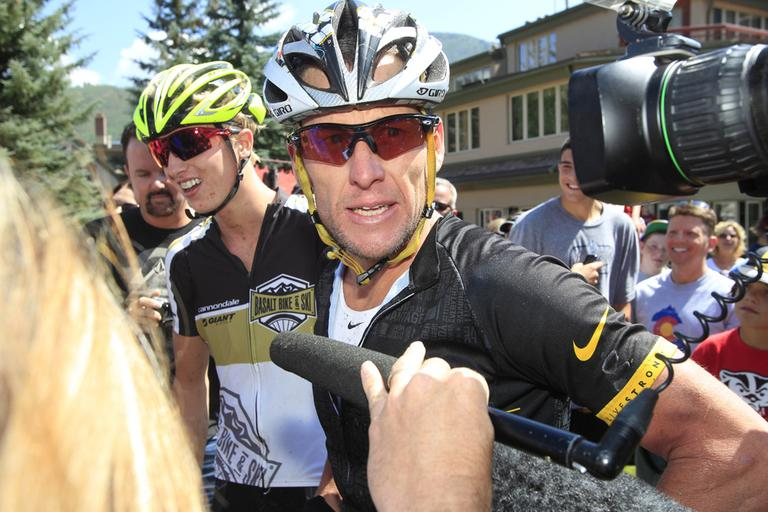 Lance Armstrong, front, talks to reporters after his second-place finish in the Power of Four mountain bicycle race in Aspen, Colo., in August. The race is the first public appearance for Armstrong since the U.S. Anti-Doping Association stripped him of his seven Tour de France championships and banned him for life from professional cycling. (AP/David Zalubowski)