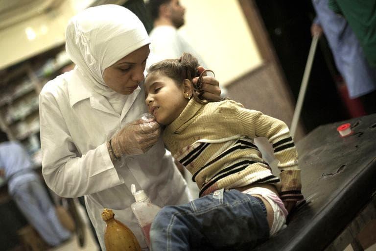 A Syrian nurse treats a girl wounded by Syrian Army artillery shelling at Dar El Shifa hospital in Aleppo, Syria, on Wednesday. (AP/Manu Brabo)