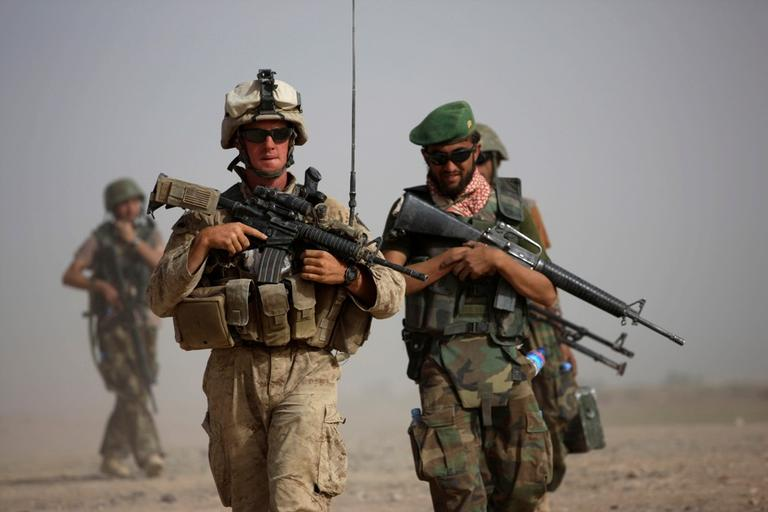 A U.S. Marine squad leader, left, walks with an Afghan National Army lieutenant during a joint patrol in Helmand province, southern Afghanistan. (AP/Brennan Linsley)