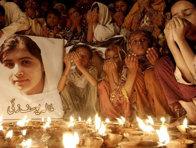 """Pakistani children pray for the recovery of 14-year-old schoolgirl Malala Yousufzai, who was shot on Tuesday by the Taliban for speaking out in support of education for women, during a candlelight vigil in Karachi, Pakistan, Friday, Oct. 12, 2012. A Pakistani military spokesman says Yousufzai is in """"satisfactory"""" condition but cautions that the next few days will be critical. Writing reads on the poster left, """"Malala Yousufzai.""""(AP)"""