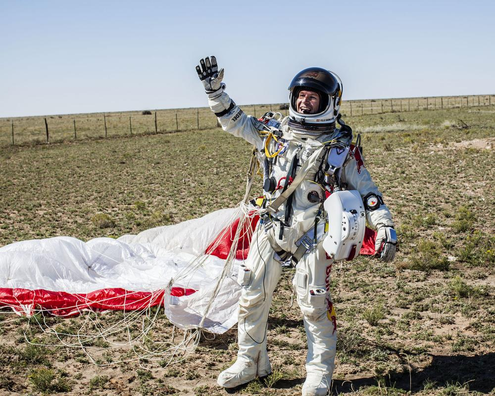 Felix Baumgartner celebrates his safe landing in the eastern New Mexico desert about nine minutes after jumping from his capsule at 128,097 feet, or roughly 24 miles, above Earth on Sunday. (Balazs Gardi/AP/Red Bull Stratos/)