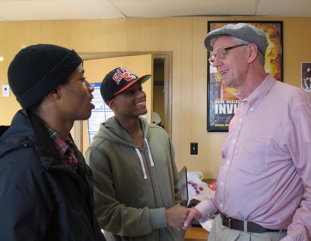 Emmett Folgert, of the Dorchester Youth Collaborative, talks with Stephen Goss and Kurt Driggs. (Monica Brady-Myerov/WBUR)