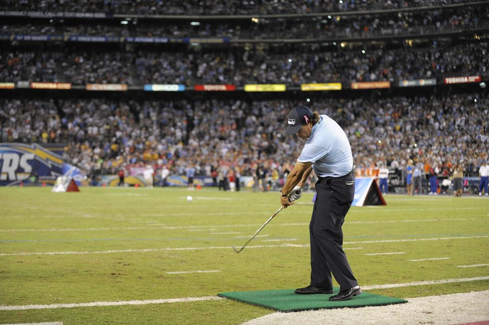 "PGA tour pro Phil Mickelson hits a tee shot for ""KPMG Chip4Charity'' in San Diego at halftime during a game between the Chargers and the Denver Broncos. (AP/Denis Poroy)"