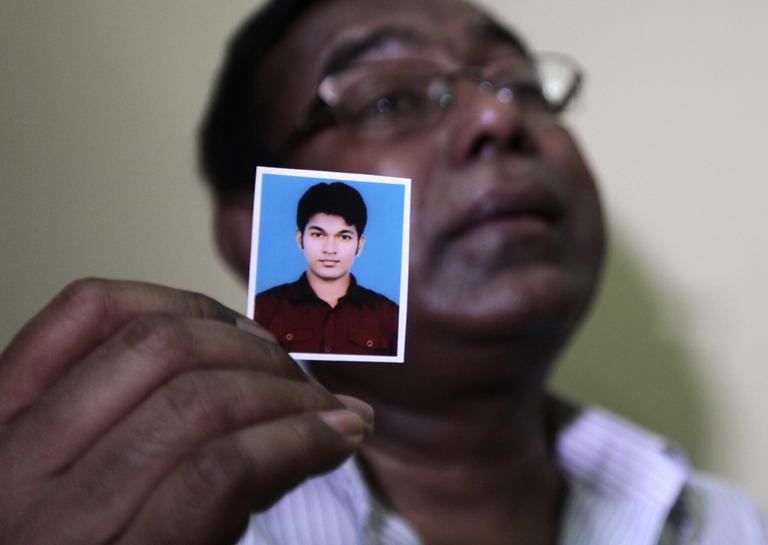Bangladeshi Quazi Ahsanullah displays a photograph of his son Quazi Mohammad Rezwanul Ahsan Nafis, as he weeps in his home in the Jatrabari neighborhood in north Dhaka, Bangladesh on Thursday. The FBI arrested 21-year-old Nafis after he tried to detonate a fake 1,000-pound car bomb, according to a criminal complaint. His family said Nafis was incapable of such actions. (AP/A.M. Ahad)