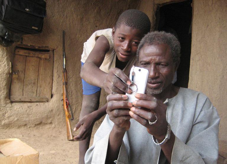 An unidentified boy helps Alaburu Maiga use his cell phone in the village of Gono, Mali. Across the developing world, cell phones are multiplying. (AP/Heidi Vogt)
