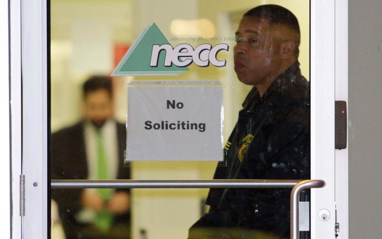 A Food and Drug Administration agent stands at the doorway of New England Compounding Center in Framingham Tuesday as investigators work inside. (Bill Sikes/AP)