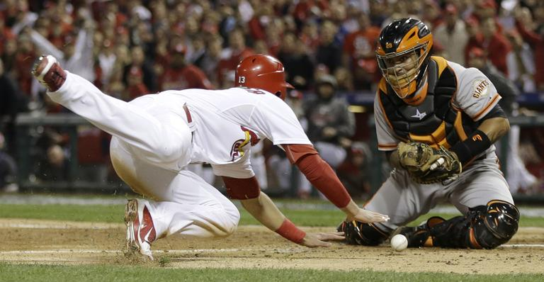 San Francisco Giants catcher Hector Sanchez can't handle the throw as St. Louis Cardinals' Matt Carpenter scores from second on a single by Matt Holliday, during the fifth inning of Game 4 of the National League championship series on Thursday. (AP/David J. Phillip)