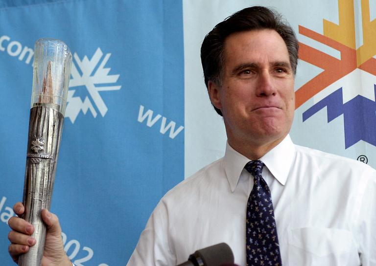 Mitt Romney holds the Olympic torch during a news conference in Salt Lake City in 2001. (Douglas C. Pizac/AP)