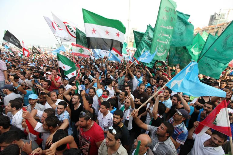 Lebanese protesters wave Syrian revolutionary flags, national flags and Islamic flags as they gather in Martyrs' Square at funeral for the country's intelligence chief, Brig. Gen. Wissam al-Hassan in Beirut, Lebanon, Sunday, Oct. 21, 2012. (Bilal Hussein/AP)