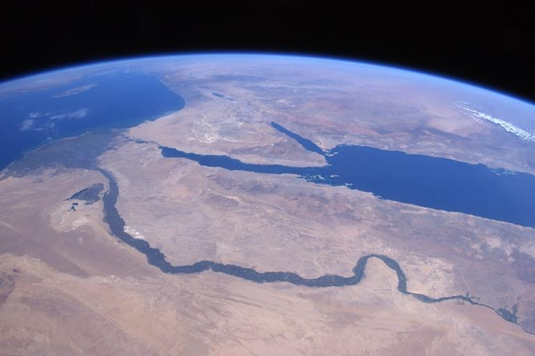 Over the Sahara Desert approaching ancient lands and thousands of years of history. The Nile River flowing through Egypt past the pyramids of Giza up to Cairo in the delta; the Red Sea, Sinai Peninsula, Dead Sea; Jordan River; and the Sea of Galilee are visible, as are the island of Cyprus in the Mediterranean Sea and Greece coming over the horizon. (NASA)