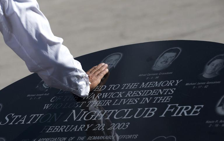 Jody King touches the image of his brother Tracy King, following a ceremony, in Warwick on Saturday held to unveil a memorial stone that honors victims of the 2003 Station Nightclub Fire.  (Gretchen Ertl/AP)