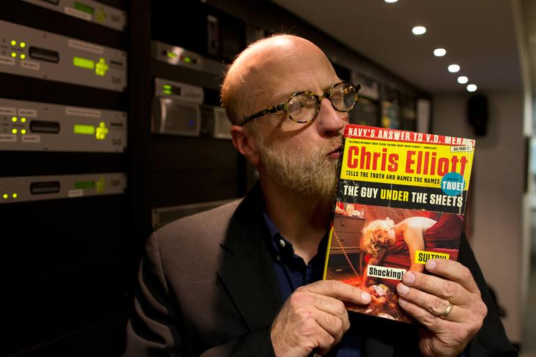 "Elliott kisses his latest book, ""The Guy Under The Sheets."" (Jesse Costa/WBUR)"