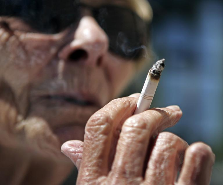Helen Heinlo smokes outside of a coffee shop in Belmont, Calif., where smoking is banned in apartment buildings and condominium developments. The law also prohibits puffing on streets and sidewalks during public events and at outdoor workplaces. (AP/Paul Sakuma)